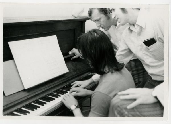 Student plays at the piano while instructors look over her shoulder and guide her, 1972