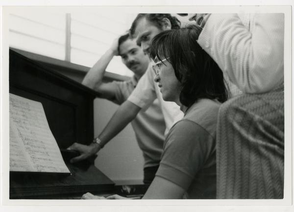 Student sits at the piano while instructors look over her shoulder during composition class, 1972