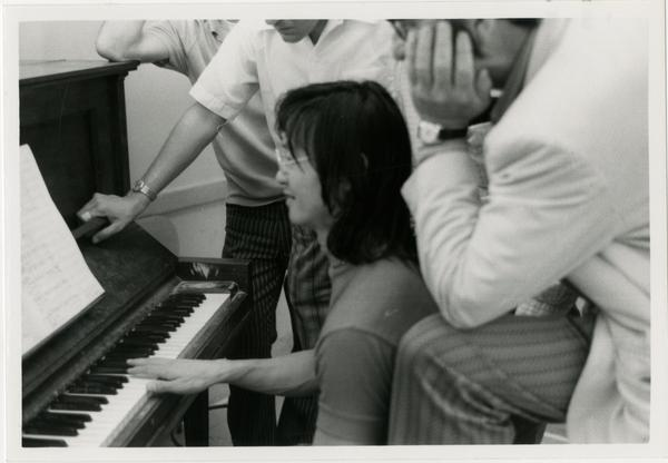 Student sits at the piano while an instructor looks over her shoulder during composition class, 1972