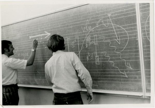 Students writing sheet music on the chalkboard during composition class, 1972