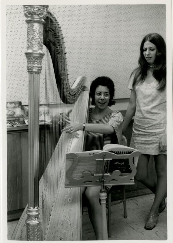 Student strums the harp while another student looks on in the practice room, 1972