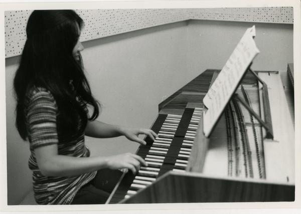 Student plays the piano in the practice room, 1972