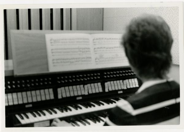 Student looks at the music sheet and plays the piano in the practice room, 1972