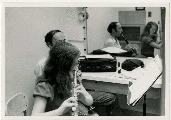 Student plays the flute while another student plays a clarinet in the practice room, 1972