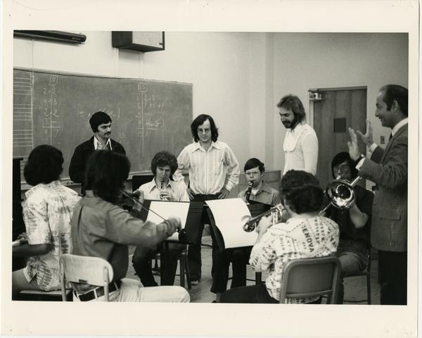 Students practice a piece in a circle as instructors look on in composition class, 1975