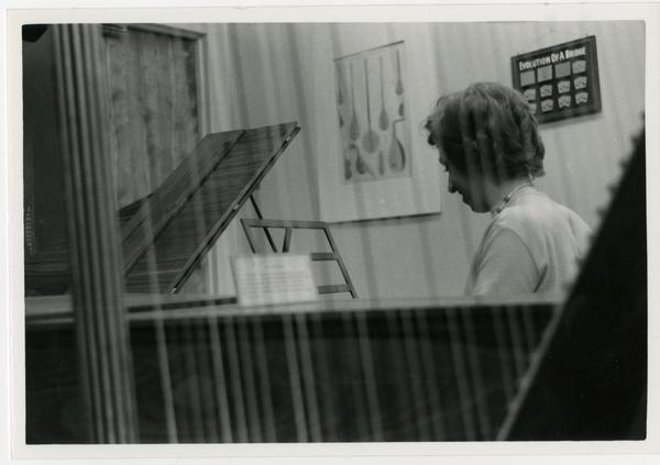 Side view of woman playing a Harpsichord