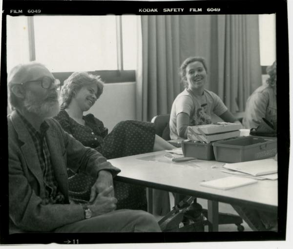 Professor John Neuhard with two students in the background as he lectures the class