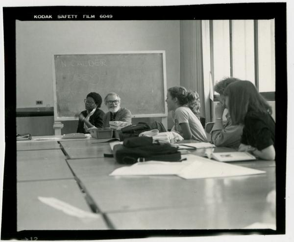 Student sitting at a table listening to Professor John Neuhard, who is sitting at the back of the table in front of the chalkboard
