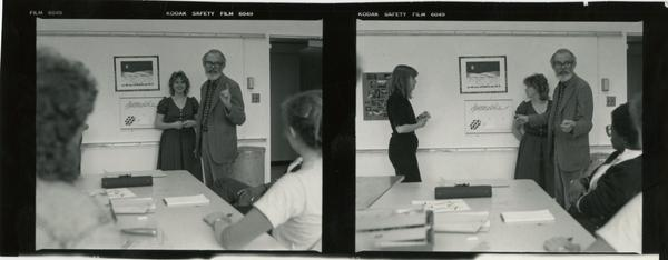 Professor John Neuhard talking with two women, possibly students, as they look at framed art on the wall