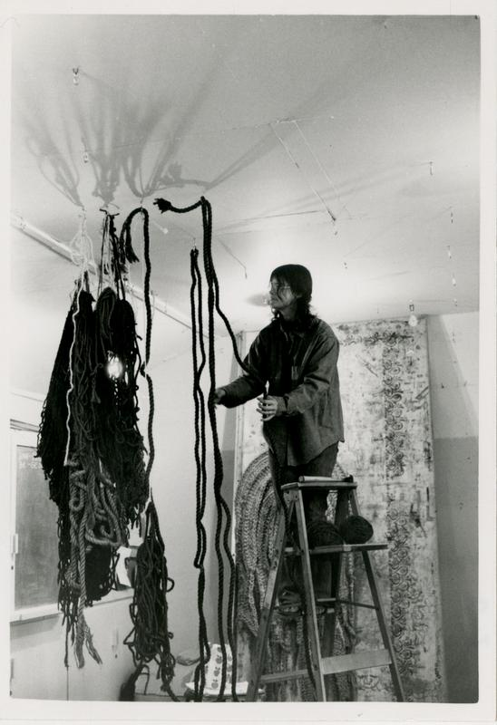 Student in Professor Kester's weaving class hanging her weaved artwork