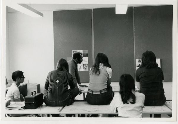 Professor Brown and a group of students examine art posters in a classroom