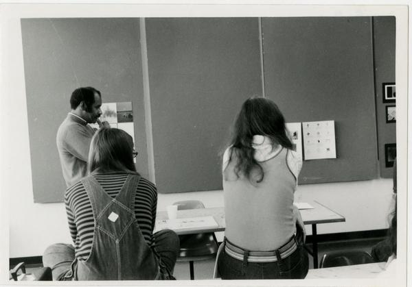 Professor Brown ponders design posters in front of him alongside two females sitting on a desk