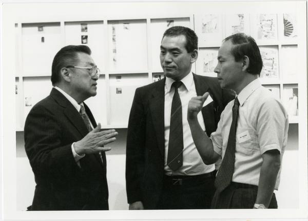 Three men talk at the Design Studio Opening