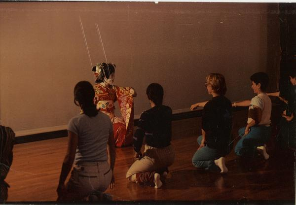 Japanese performer in front of kneeling students