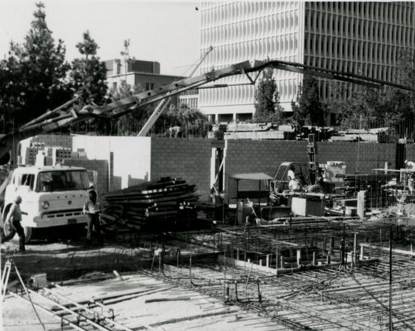 Construction workers and equipment on site of Schoenberg Hall with a view of Young Research Library and Bunche Hall in the background