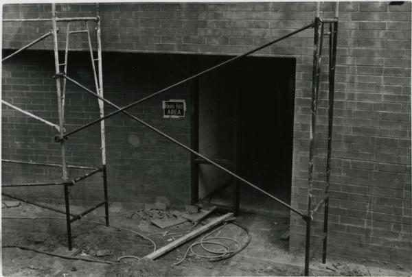 "View of side entrance of Schoenberg Hall with ""Hard Hat Area"" sign"