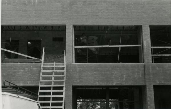 Looking up at second floor of Schoenberg Hall during construction with construction worker on ladder