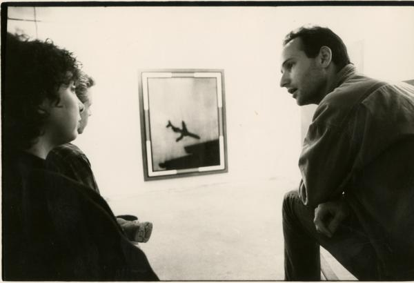Three people discussing artwork at center