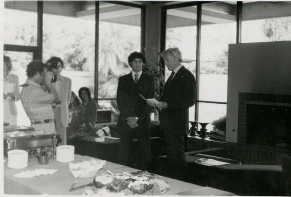 Speaker and unidentified man stand at front of the room during Goldwyn Reception, May 1981