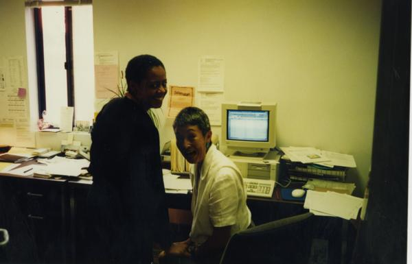 Two members of Dean's OFC Staff posing in front of computer