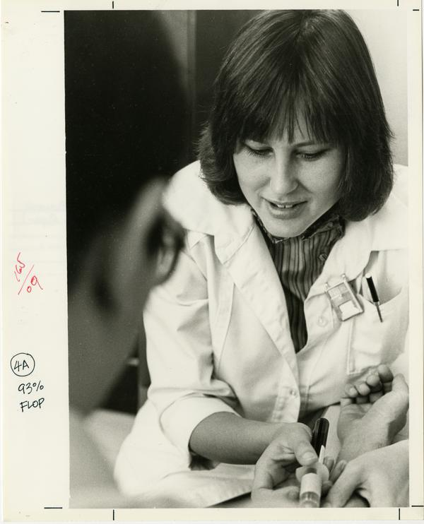 AIDS research: Researcher drawing blood from subject, 1983