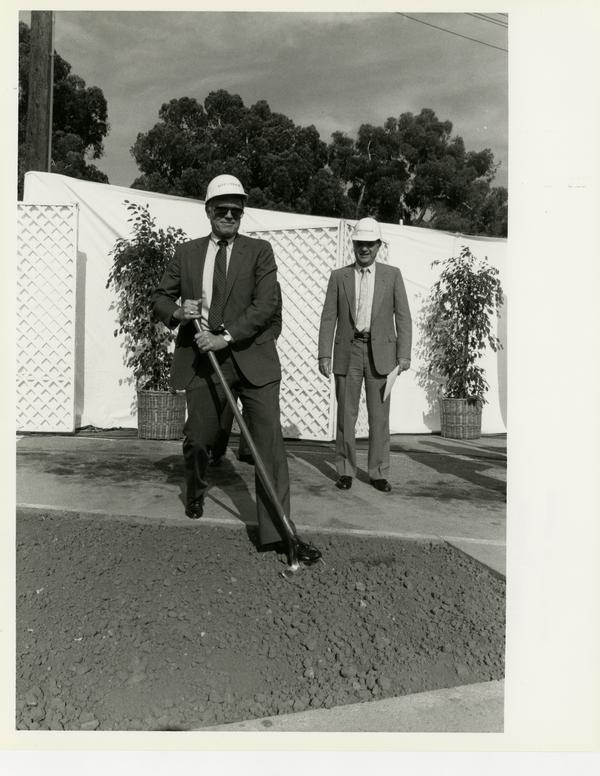 Unidentified man shovels dirt at the groundbreaking of the UCLA Ambulatory Care Complex