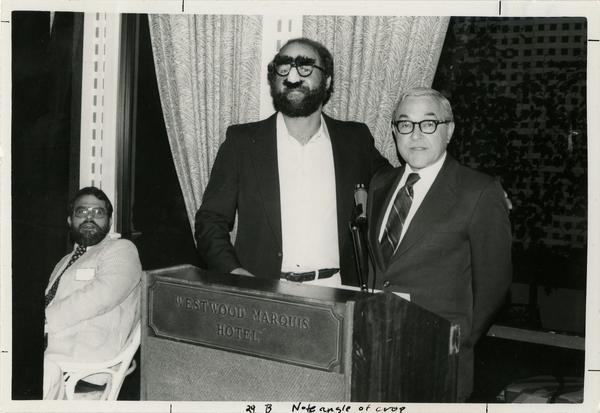 Two unidentified males behind a Westwood Marquis Hotel podium while a third male sitting in a chair