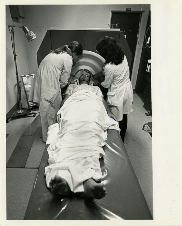 Two doctors position patient for the Computerized Tomography Simulater