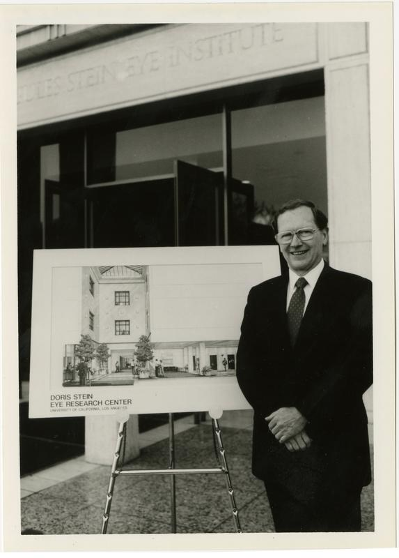Man stands in front of partial rendering of Doris Stein Eye Research Center building