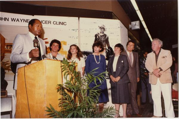 Speaker at podium at opening event for John Wayne Cancer Clinic, 1981
