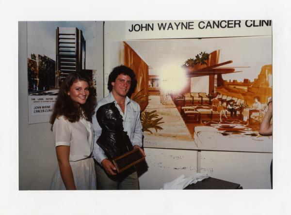 Patrick and Marisa Wayne pose with John Wayne bust at opening of John Wayne Cancer Clinic