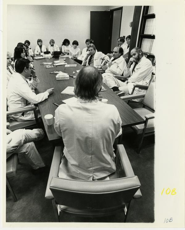 Doctors seated around conference table at Jonsson Comprehensive Cancer Clinic event, 1981
