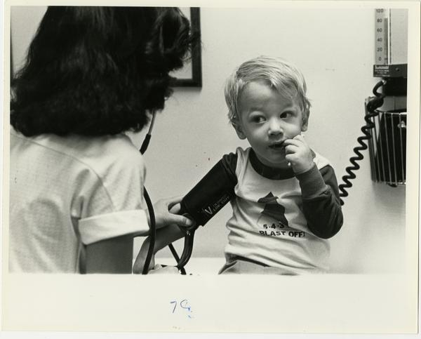 Doctor measures child's blood pressure