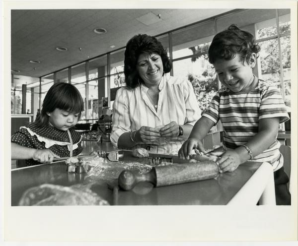 Woman interacting with two children at the Marion Davies Children's Center