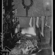 Montage photograph of Mawby triplets in front of fireplace with Christmas tree and stockings, [Santa Monica, 1929]