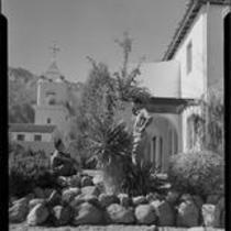 Woman and man in rock garden, El Mirador Hotel, Palm Springs, 1935