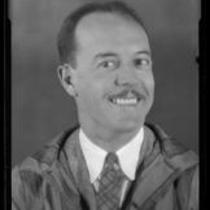 Portrait of Darrel B. Foss, smiling in suit, tie, and striped overcoat, 1924