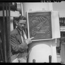 Man pointing to plaque on mast of S.S. Constitution, San Diego Harbor, San Diego, 1934