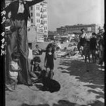 Clown on stilts with children on beach, Santa Monica, 1928