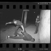 77th Street Division police officers arresting and searching suspect in Los Angeles, Calif., 1989